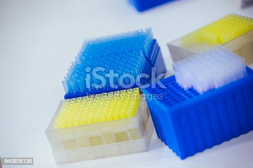 istock blue and yellow tip for scientific experiment in the boxes 940926136