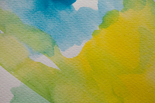 1084390994 istock photo Blue and yellow watercolor background. Abstract watercolor background on textured paper. Hand painted blue and yellow watercolor. 1011356412
