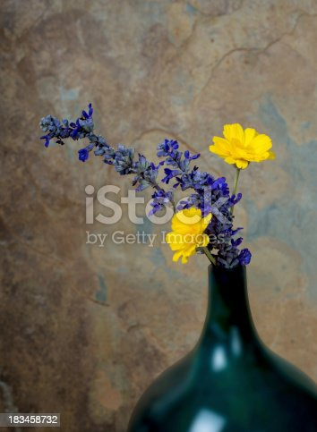 Blue and yelow wildflowers in a turquoise vase against a rustic slate background