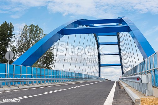 Blue arch brodge with barrier of both side of road.