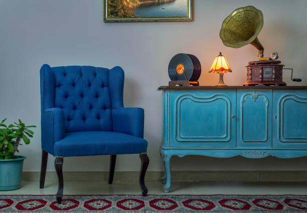 blaue sessel, vintage anrichte aus holz hell blau, beleuchtete antike tischlampe, alten plattenspieler (gramophone), vinyl-schallplatten auf hintergrund beige wand, porzellan gefliesten boden und roter teppich - teppich hellblau stock-fotos und bilder