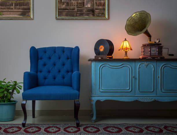 blaue sessel, vintage anrichte aus holz hell blau, beleuchtet, antike tischlampe, alten plattenspieler (gramophone) und vinyl-schallplatten - teppich hellblau stock-fotos und bilder