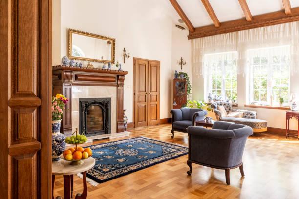blaue sessel und gemusterten teppich aus holz kamin in anspruchsvolle interieur. echtes foto - teppich englisch stock-fotos und bilder