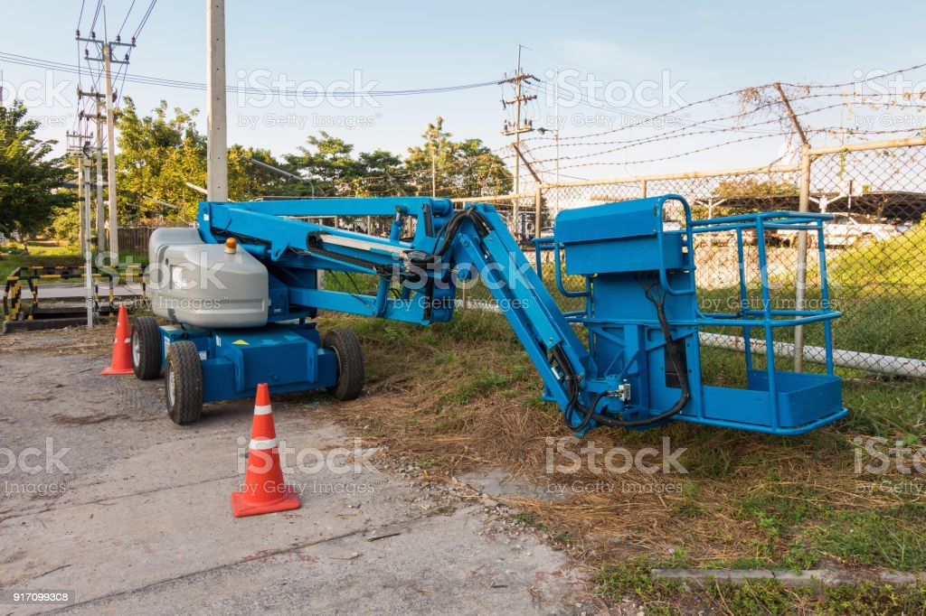 Blue articulated boom lift for construction work stock photo