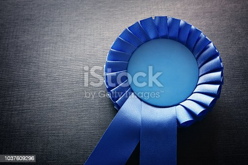 Blue award rosette with ribbons and copy space on black background