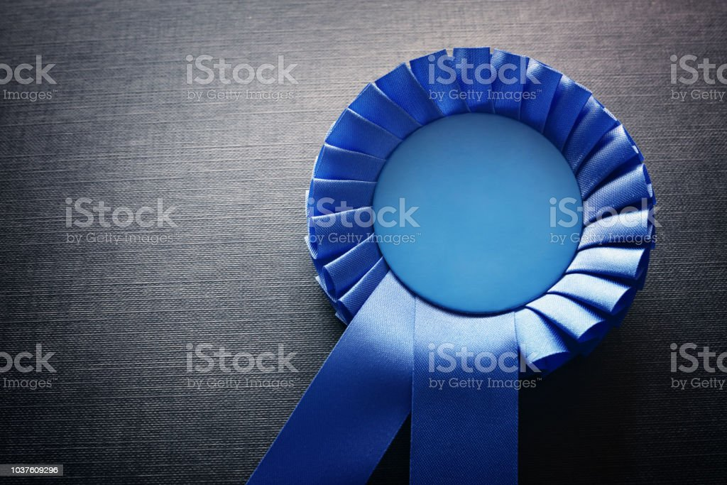 Blue award rosette with ribbons and copy space stock photo