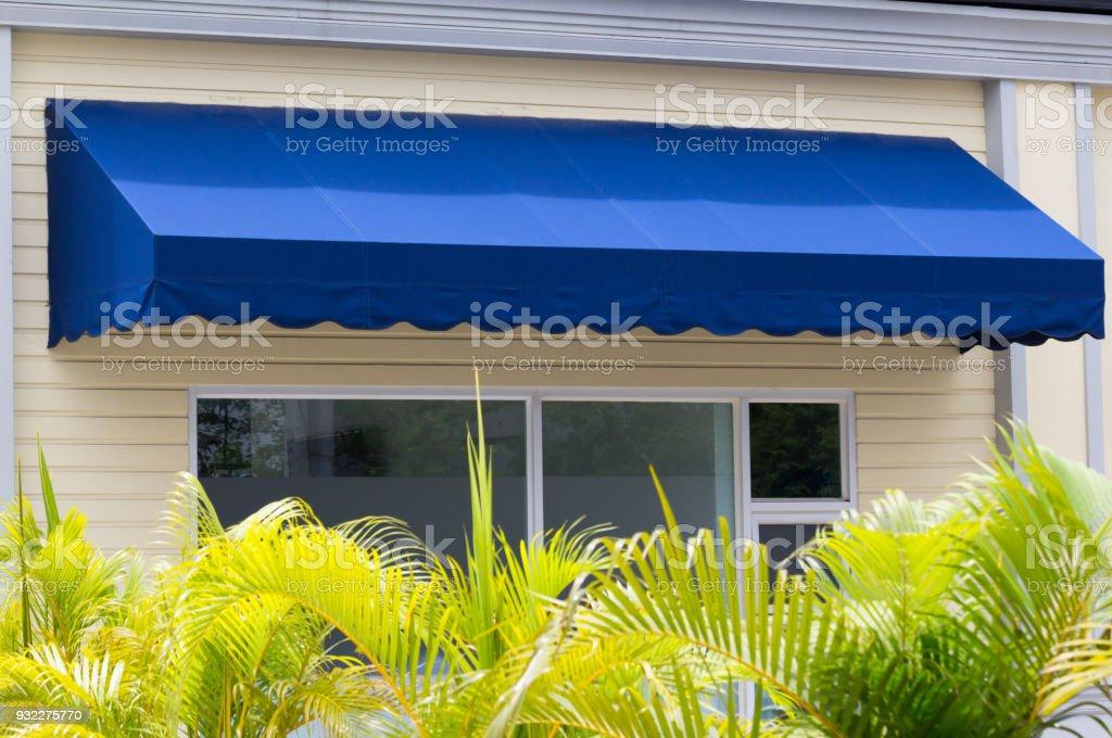 blue awning over white aluminium frame window of shop stock photo