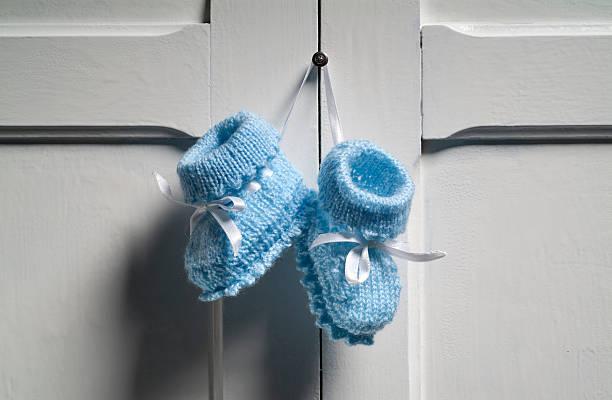 Blue Baby Booties hanging on white door stock photo