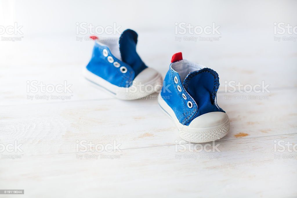 blue baby sneakers on a wood floor stock photo
