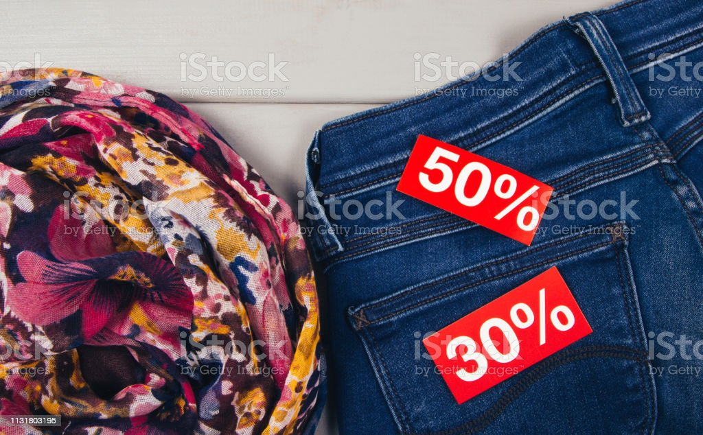 30, 50% off on red paper in the pocket of blue denim jeans.