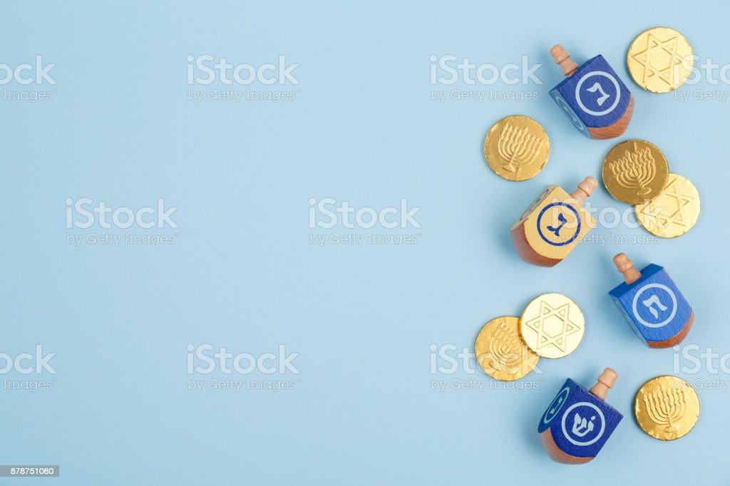 多色 dreidels とチョコレートのコインと青色の背景色。ハヌカとユダヤ人の休日の概念。 ストックフォト