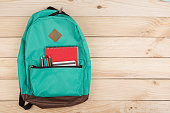 Education concept - blue backpack, red notebooks and pencils on wooden table