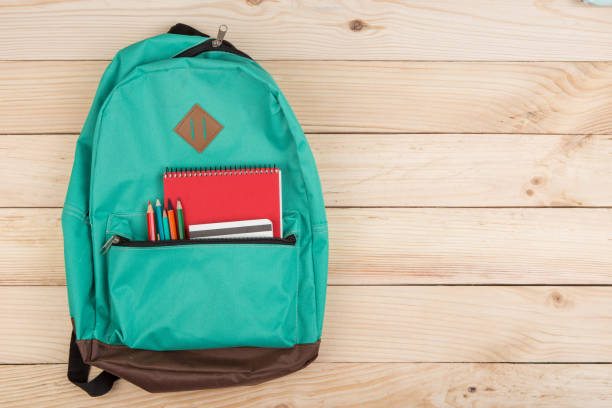 木桌上的藍色背包、紅色筆記本和鉛筆 - 背囊 個照片及圖片檔