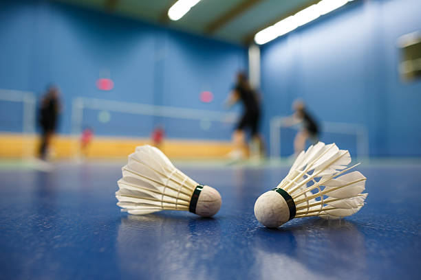 Blue badminton court and shuttlecocks with players competing badminton courts with players competing; shuttlecocks in the foreground (shallow DOF; color toned image) badminton stock pictures, royalty-free photos & images
