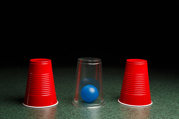 Blue Ball Hidden Under Clear Cup Life is easy when you know the answers.  Location of blue ball is revealed by clear cup.  Copy space in upper half of the frame fades to black.  This concept photo could be applicable to many concepts including – risk, reward, seeking answers, finding solutions, decision making, gaming, and many others. shell game stock pictures, royalty-free photos & images