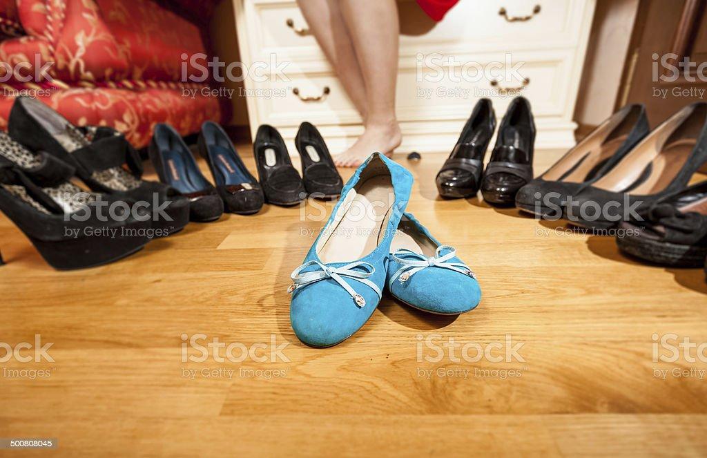 blue ballet flats standing among black high heel shoes stock photo