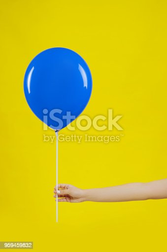 istock blue balloon in woman hand on yellow background. 959459832
