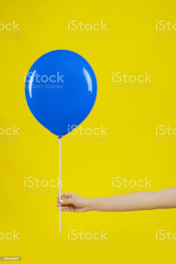 blue balloon in woman hand on yellow background. stock photo