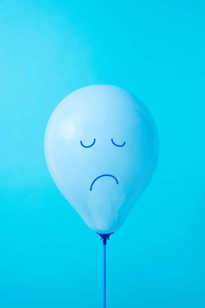 palloncino blu con un viso triste - blue monday foto e immagini stock