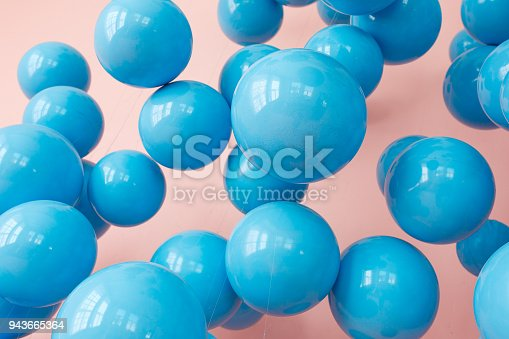 945748362 istock photo blue balloons, blue bubbles on pink background. Modern punchy pastel colors. Close up shot with shiny reflection 943665364