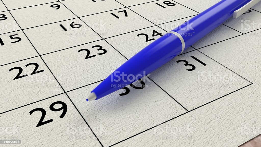 Blue ballpen on a paper calendar closeup stock photo