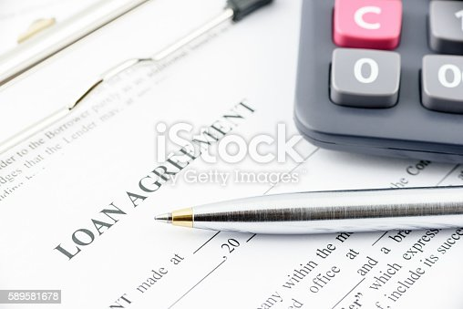 istock Blue ballpoint pen and a calculator on a loan agreement. 589581678