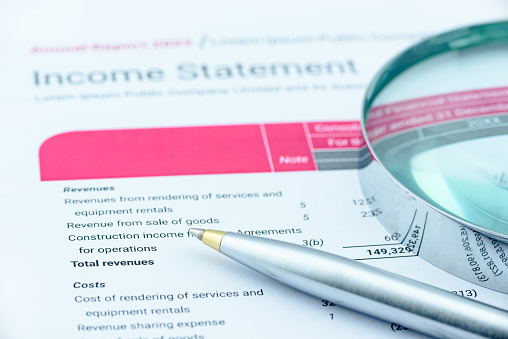 897644798 istock photo Blue ballpoint pen and a magnifier on an income statement. 530770414