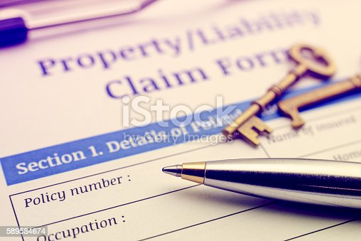 1128824554 istock photo Blue ballpoint pen and a property / liability claim form. 589584674