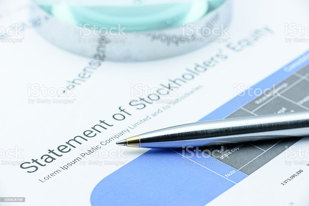 Blue ballpoint pen on a company's statement of stockholders' equity. stock photo