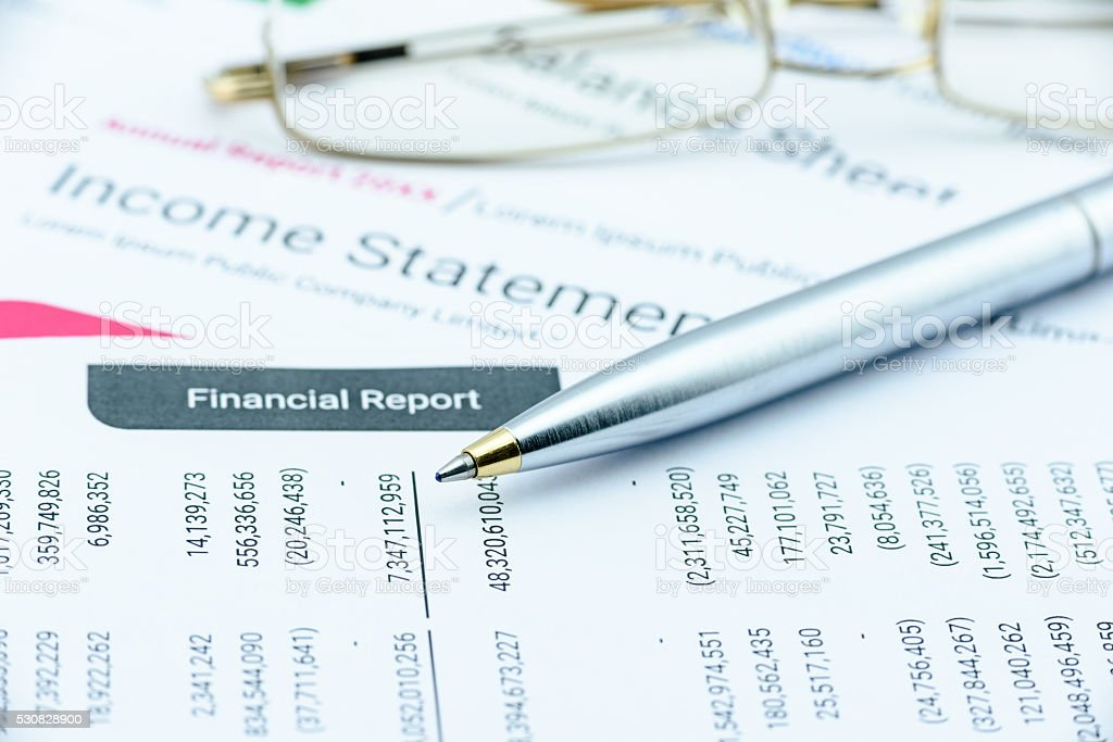 Blue ballpoint pen on a quarterly corporate financial report. stock photo