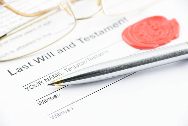 Blue ballpoint pen on last will and testament. Blue ballpoint pen on last will and testament with eye glasses and a sealing wax stamped with alphabet letter B. Preparation for filling and signing a document. last stock pictures, royalty-free photos & images