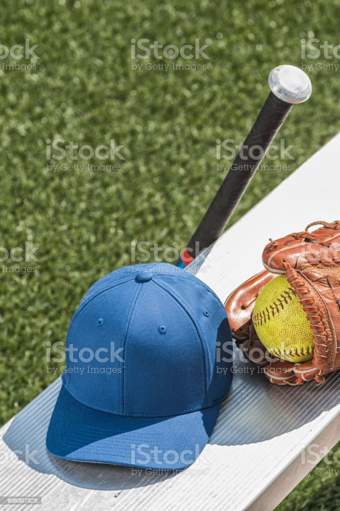 Looking down at a worn yellow softball in a brown leather glove with...
