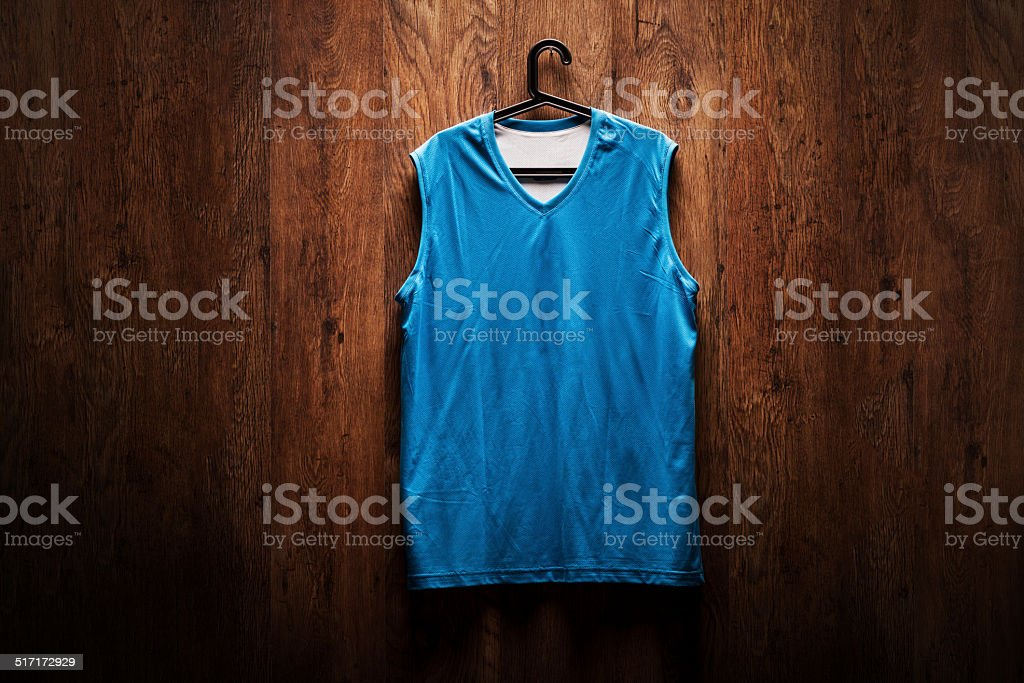 Blue basketball jersey hanging on a wooden wall stock photo