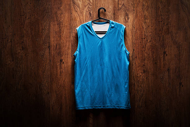 blue basketball jersey hanging on a wooden wall - sports uniform stock photos and pictures