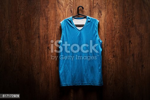 blue basketball jersey hanging on a wooden wall stock photo more pictures of basketball. Black Bedroom Furniture Sets. Home Design Ideas