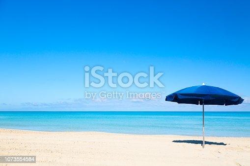 Blue beach umbrella parasol on the tropical beach. Vacation background