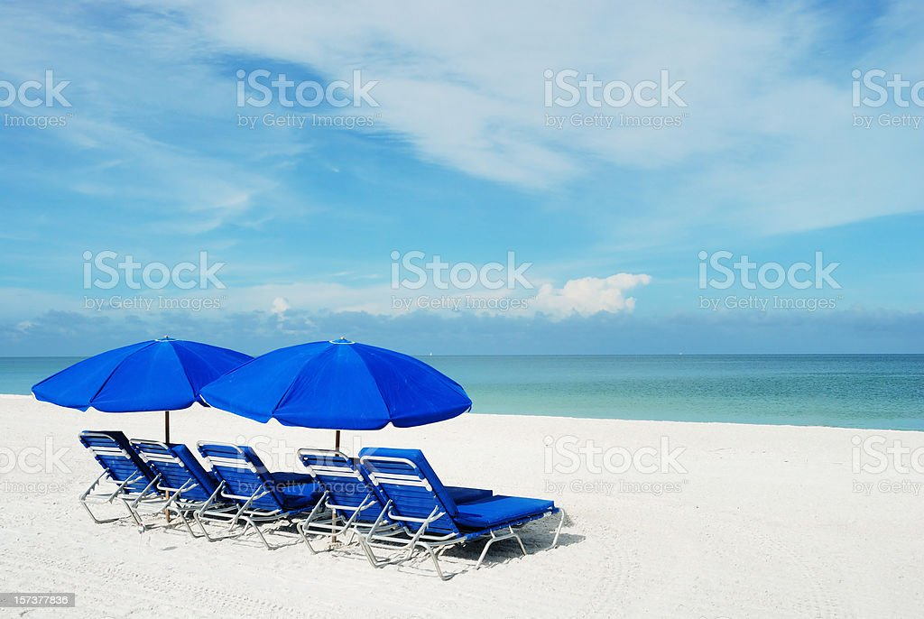 Blue beach umbrellas on a white sandy beach. royalty-free stock photo