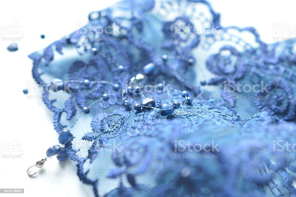 Blue beads lying on lace fabric stock photo