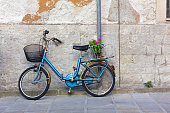 Blue vintage bicycle against an exterior wall with a flowerpot in its rear basket