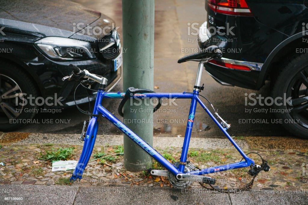 Blue bicycle attached to street pillar with lock stands without wheels after being stolen in the German capital stock photo