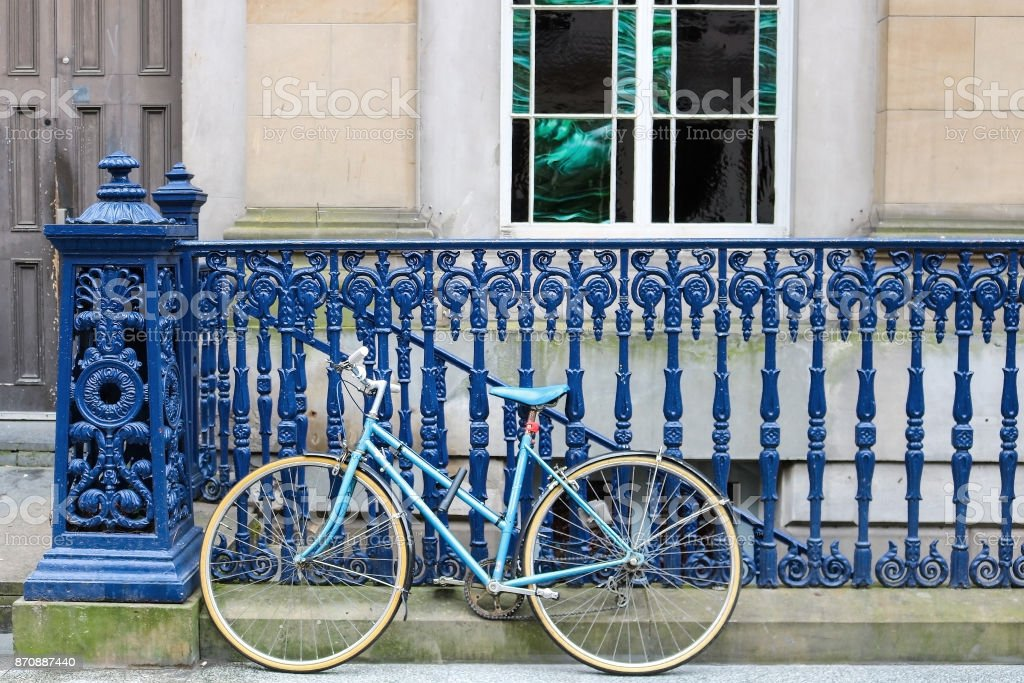 Blue Bicycle Rests Against Dark Blue Iron Fence on Sidewalk stock photo