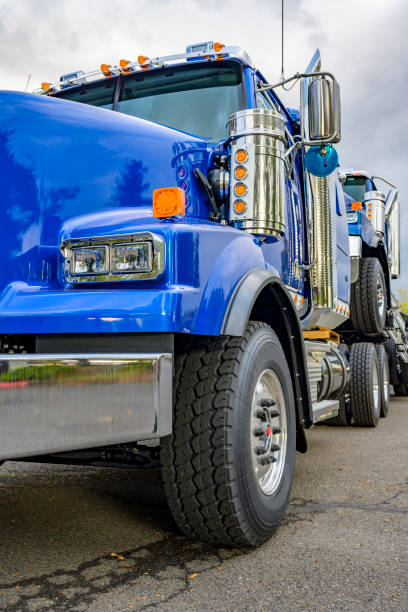 Blue big rig semi truck towing another semi truck tractor on the chassis frame stock photo