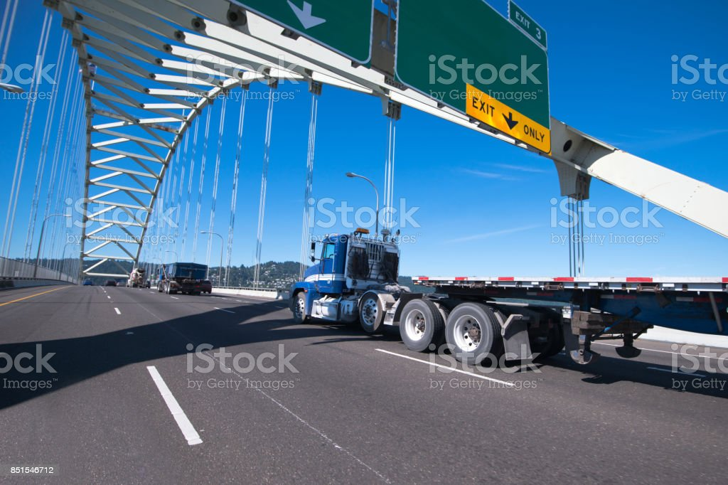 Blue big rig semi truck with day cab and flat bed semi trailer driving on the arched bridge stock photo