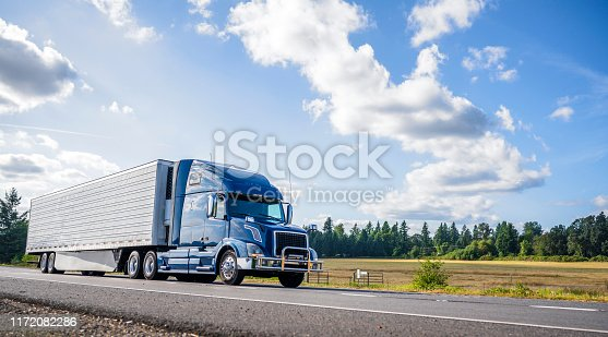 Big rig powerful professional industrial blue bonnet semi truck for long haul delivery commercial cargo going with refrigerator semi trailer on the summer road with forest and meadows on the sides