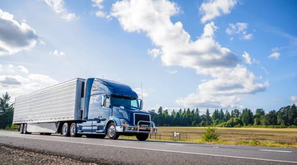blaue große rig semi truck mit grillwache trabsporting gefrorene fracht im kühlschrank sattelauflieger mit rock spoiler läuft auf der geraden straße - schweres nutzfahrzeug stock-fotos und bilder