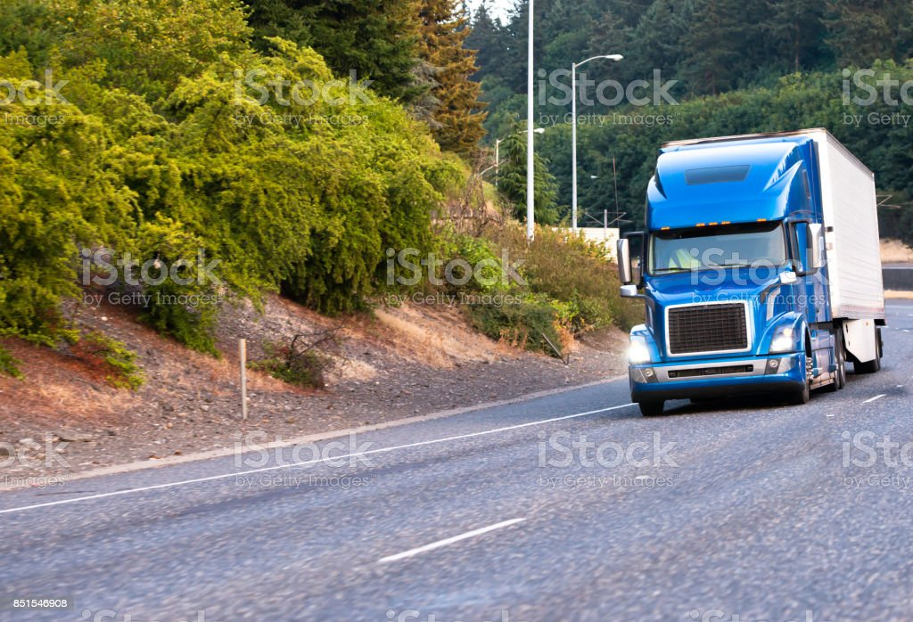 Blue big rig semi truck with reefer trailer moving on wide highway with green trees on the shoulder stock photo