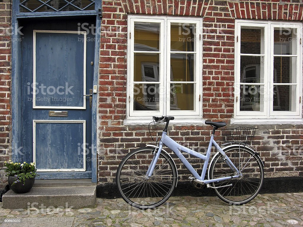 A blue bike sitting outside a house with a blue door royalty-free stock photo