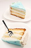 Two pieces of blue birthday cake isolated on white. Selective focus.