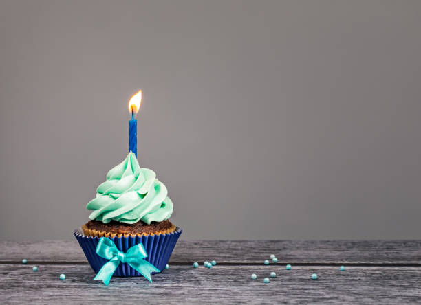 Blue Birthday Cupcake Blue Cupcake with bow, sprinkles and one candle over a gray background. first birthday stock pictures, royalty-free photos & images
