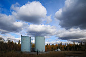 Oil lease of blue bitumen tanks in a field under a clouded sky
